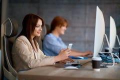 Дизайнер женщины используя smartphone пока работающ с компьютером Стоковое фото RF