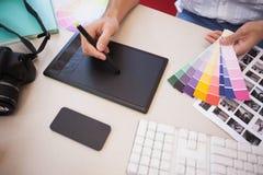 Дизайнер используя таблетку графиков и диаграммы цвета Стоковое Фото