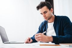 Дизайнер молодого человека работая на современной студии просторной квартиры сидя на таблице пока работающ на ноутбуке стоковое фото