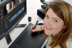 Дизайнер молодой женщины используя таблетку графиков Стоковая Фотография