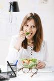 Дизайнер молодой женщины творческий есть салат в офисе. Стоковые Изображения