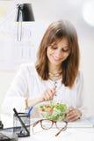 Дизайнер молодой женщины творческий есть салат в офисе. Стоковые Изображения RF