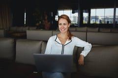 Дизайнер молодой счастливой женщины творческий используя портативный компьютер для конструировать интерьер в новой кофейне, Стоковые Изображения