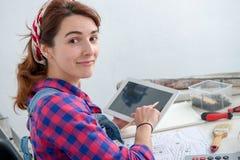 Дизайнер по интерьеру молодой женщины используя цифровую таблетку Стоковые Изображения