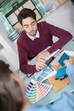 Дизайнер по интерьеру показывая колесо цвета к клиенту в студии Стоковая Фотография