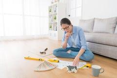 Дизайнер сидя на поле живущей комнаты деревянном Стоковые Фотографии RF