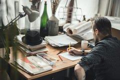 Дизайнер человека работая в офисе стоковая фотография
