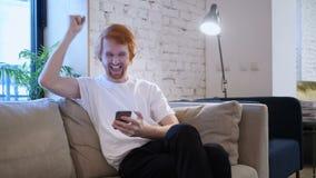 Дизайнер Redhead творческий возбужденный для успеха пока использующ Smartphone сток-видео