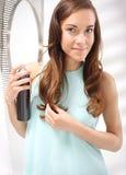 Дизайн волос - брюнет чистя ее волосы щеткой перед зеркалом Стоковые Фотографии RF