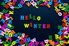 Дизайн концепции - ЗИМА слова ЗДРАВСТВУЙТЕ! от пестротканых деревянных писем на черной предпосылке, творческой идее Стоковые Фото