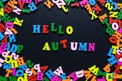 Дизайн концепции - ОСЕНЬ слова ЗДРАВСТВУЙТЕ! от пестротканых деревянных писем на черной предпосылке, творческой идее Стоковое Изображение