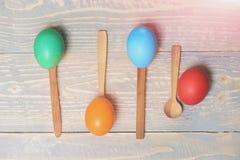Дизайн меню, еда пасхи, красочные покрашенные яичка в деревянных ложках Стоковые Фото