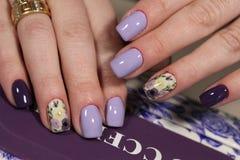 Дизайн пурпура маникюра с картиной цветков Стоковые Изображения