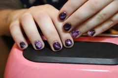 Дизайн пурпура маникюра с картиной цветков Стоковые Фото