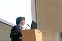 Диктор давая беседу на подиуме на бизнес-конференции Стоковое Фото
