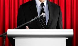 Диктор давая речь на семинаре с красной предпосылкой занавеса Стоковое фото RF
