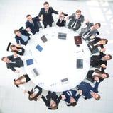 Директор и дело объединяются в команду сидеть на круглом столе и держать руки ` s одина другого Стоковое фото RF