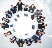 Директор и дело объединяются в команду сидеть на круглом столе и держать руки ` s одина другого Стоковые Фото