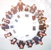 Директор и дело объединяются в команду сидеть на круглом столе и держать руки ` s одина другого Стоковые Изображения RF