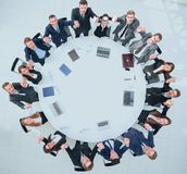 Директор и дело объединяются в команду сидеть на круглом столе и держать руки ` s одина другого Стоковые Фотографии RF