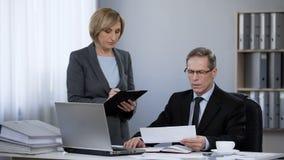 Директор и его секретарша в офисе, планируя план-графике, давая инструкции стоковое фото rf