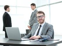 Директор сидит на таблице с открытой компьтер-книжкой и бумагами Стоковые Фото