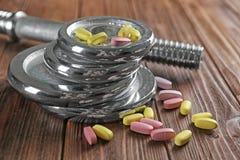 Диски и лекарства веса на деревянной предпосылке стоковое фото rf