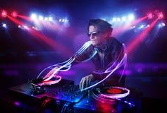 Диск-жокей играя музыку с светлыми фокусировками коротких волн на этапе стоковые фотографии rf