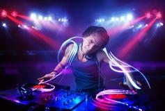 Диск-жокей играя музыку с светлыми фокусировками коротких волн на этапе стоковая фотография rf