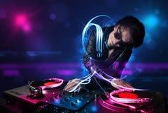 Диск-жокей играя музыку с electro световыми эффектами и светами стоковое фото
