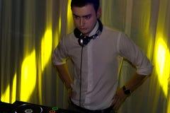 Диск-жокей на клубе стоя над его палубой музыки Стоковое Изображение RF