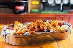 Диск с goujons цыпленка, кудрявое chook подгоняет, сосиски коктеиля, блинчики с начинкой veg, кольца лука & фраи, который служат  стоковые изображения