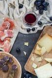 Диск с omemade трудных сыров высушил мясо, serrano jamon ветчины или crudo ветчины, стекло красного вина с виноградинами Стоковые Изображения