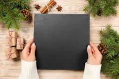 Диск шифера владением руки Famale на коричневой предпосылке с украшением рождества шифер доски Новый Год принципиальной схемы стоковые фотографии rf