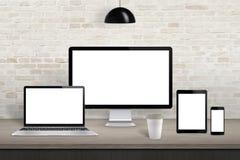 Дисплей компьютера, компьтер-книжка, таблетка и мобильный телефон с экраном на столе офиса стоковые фото