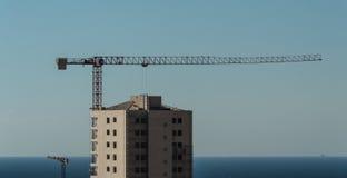 Дистантный взгляд здания с краном башни Стоковая Фотография