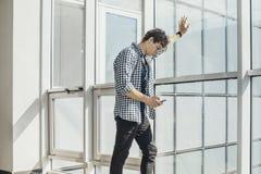 Дистантный план молодого человека смотря экран мобильного телефона на станции метро стоковое фото