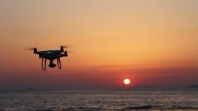 Дистанционного управления трутень с летанием в небе захода солнца акции видеоматериалы