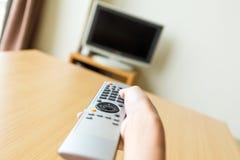 Дистанционное управление ТВ владением руки стоковое изображение rf