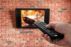 Дистанционное управление ТВ в руке и кирпичной стене на заднем плане стоковое изображение