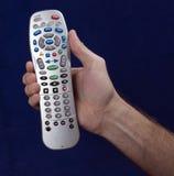 Дистанционное управление в руке с голубой предпосылкой Стоковая Фотография