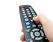 Дистанционное управление ТВ в крупном плане изолированном рукой стоковые изображения
