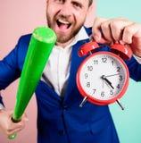 Дисциплина и санкции Будильник и бейсбольная бита владением стороны босса агрессивные Часы владением костюма человека в руке и стоковая фотография