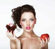 Дилемма. Диета. Нерешительная женщина с Яблоком и пирожным стоковое фото