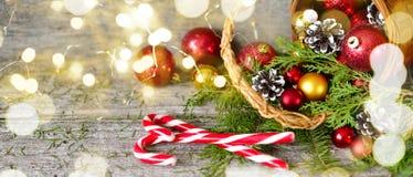 Длинная корзина рождества знамени с подарками и сияющими светами Красные шарики, конусы сосны, леденец на палочке на деревянном с Стоковая Фотография RF