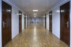 Длинная прихожая офиса с много дверей темноты - красной древесиной Стоковые Изображения