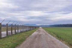 Длинная проселочная дорога идя прямой дальше с загородкой на праве стоковое изображение rf