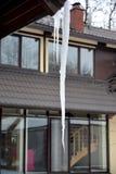 Длинная сосулька которая опасно висит вниз от крыши Стоковое Изображение RF