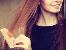 Длинная с волосами девушка расчесывая ее волосы красоты Стоковое Изображение RF