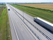 Длинная тележка полуприцепа корабля управляя на шоссе прямо 4 майн проходя в луг стоковое изображение
